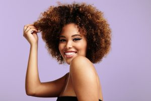 woman with a round afro hair touching a part of it and laughing